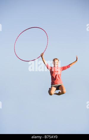 11 year old girl jumps high with hula hoop, Winnipeg, Manitoba, Canada - Stock Photo
