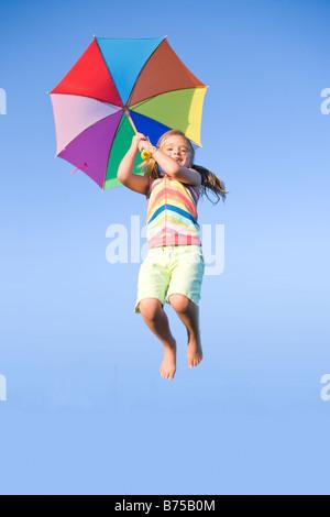 Six year old girl jumping with umbrella, Winnipeg, Manitoba, Canada - Stock Photo