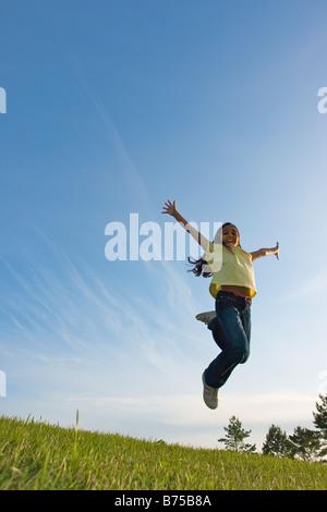 8 year old girl jumping, Winnipeg, Canada - Stock Photo
