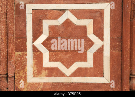 A decorative eight pointed star in a square made from white marble inlaid in red sandstone. - Stock Photo