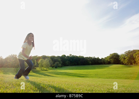 Eight year old girl running in park, Winnipeg, Canada - Stock Photo