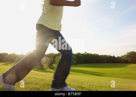 Lower portion of eight year old girl running in park, Winnipeg, Canada - Stock Photo
