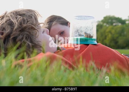 Six year old boy and 8 year old girl, laying on grass with frog in collecting jar, Winnipeg, Canada - Stock Photo