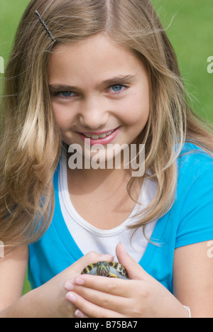 Eight year old girl holding turtle, Winnipeg, Canada - Stock Photo