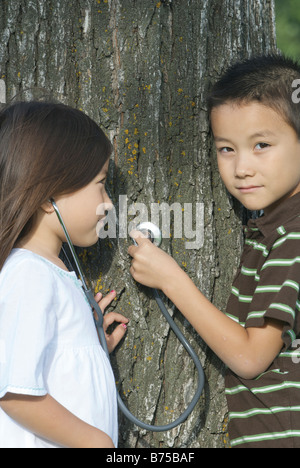 Five year old sister and seven year old brother with stethescope on tree, Winnipeg, Canada - Stock Photo