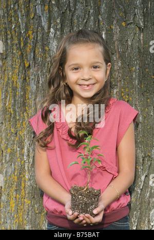 Seven year old girl holding seedling beside tree, Winnipeg, Canada - Stock Photo