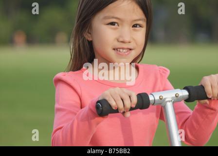 Six year old girl on scooter, Winnipeg, Canada - Stock Photo