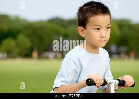 Eight year old boy on scooter, Winnipeg, Manitoba, Canada - Stock Photo