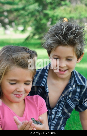 Eight year old boy and six year old girl with turtle, Winnipeg, Canada - Stock Photo