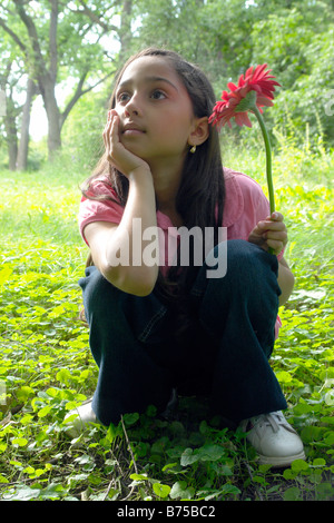 Eight year old girl in clearing with flower, Winnipeg, Canada - Stock Photo