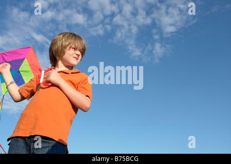Six year old boy holding kite, Winnipeg, Canada - Stock Photo