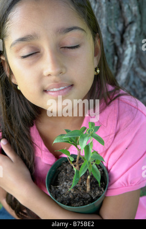Eight year old girl with closed eyes holding small tree beside large tree, Winnipeg, Canada - Stock Photo