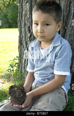 Six year old boy holds small tree, seated beside large tree, Winnipeg, Canada - Stock Photo