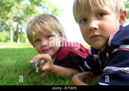 Four and six year old brothers holding turtle, Winnipeg, Canada - Stock Photo