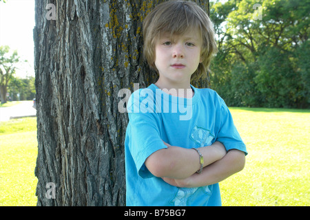 Six year old with arms crossed stands beside tree, Winnipeg, Canada - Stock Photo