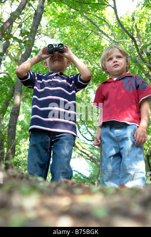 Four and six year old brothers on walking trail in forest, Winnipeg, Canada - Stock Photo