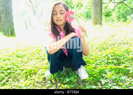 Eight year old girl in clearing with flower, Winnipeg, Manitoba, Canada - Stock Photo