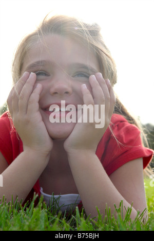 Six year old girl with chin in hands lying on grass, Winnipeg, Manitoba, Canada - Stock Photo