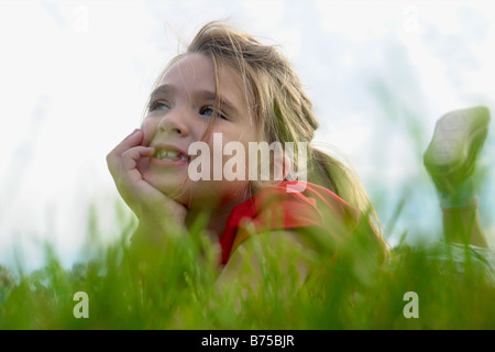 Six year old girl with chin in hands lying on grass, Winnipeg, Canada - Stock Photo