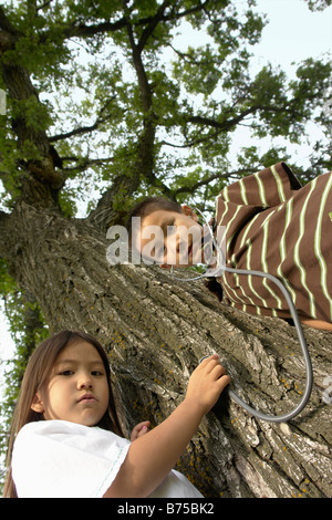 Low angel, five and seven year old sister and brother with stethescope on tree, Winnipeg, Canada - Stock Photo