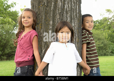 Seven and five year old girls and seven year old boy hold hands around tree, Winnipeg, Canada - Stock Photo