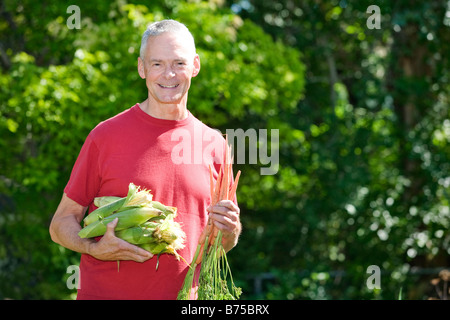 Senior man holding ears of corn and carrots, Winnipeg, Canada - Stock Photo