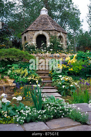 Flagstone steps over pool and mixed herbaceous planting leading to a Cotswold stone folly - Stock Photo