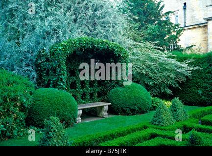 Garden bench in the Knot Garden at Bourton House - Stock Photo