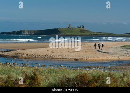 The distant ruins of Dunstanburgh Castle on the Northumberland coast UK - Stock Photo