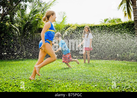 Three friends playing in a lawn - Stock Photo