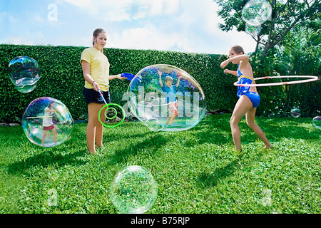 Four friends playing with bubbles and plastic hoop - Stock Photo
