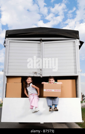Portrait of a boy and a girl sitting in a truck and smiling - Stock Photo