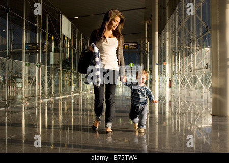 young mother arriving with toddler at european airport - Stock Photo