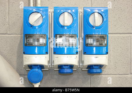 three phase electrical sockets on factory wall - Stock Photo