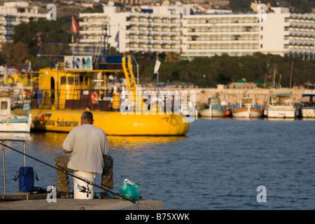 Man fishing by marina, with yellow submarine, boats and apartment blocks in background, Aya Napa, Cyprus - Stock Photo