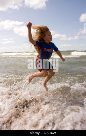 Young girl in wetsuit playing in water and jumping above the surf at the beach - Stock Photo