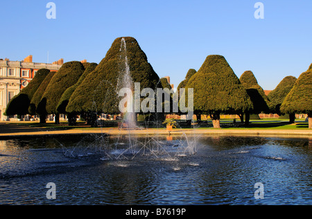 Water fountain and yew trees in Hampton Court Palace gardens Surrey - Stock Photo