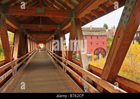 Couple in Covered Bridge with Red Mill, Littleton, New Hampshire, USA - Stock Photo