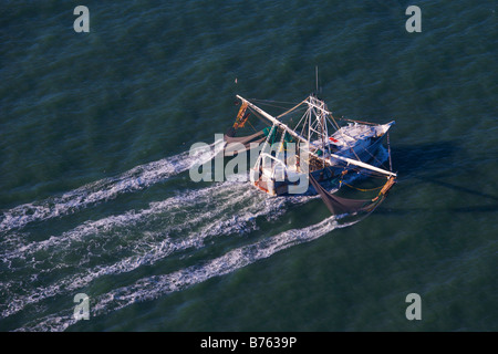 Aerial view of a shrimp boat nets dropped working the water off the coast of Charleston South Carolina - Stock Photo