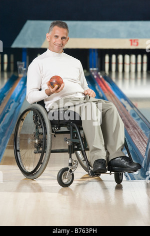 Portrait of a disabled mature man holding a bowling ball and smiling - Stock Photo