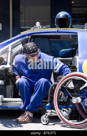 Disability driver getting into wheelchair from racing car - Stock Photo