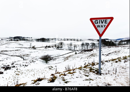 Give Way road sign in snowy landscape - Stock Photo