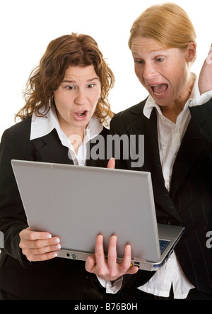 two angry businesswoman women with laptop - Stock Photo