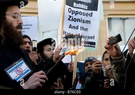 Rabbi Greenberg  holds his burning Israeli passport  at a protest against the bombing of Gaza - Stock Photo