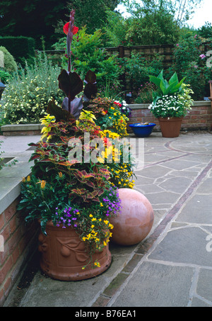 Terracotta ball and containers planted in hot colours on a stone terrace - Stock Photo