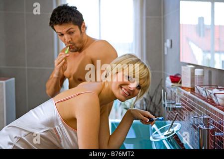 Paar beim Zaehneputzen im Badezimmer, couple with toothbrush in the bathroom - Stock Photo