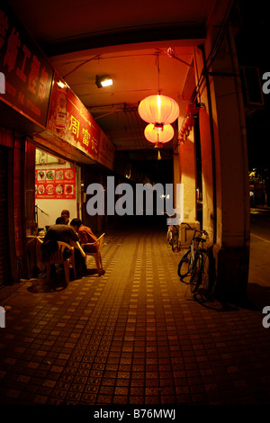 Family eating dinner dinner together late at nighe in Guangzhou China - Stock Photo