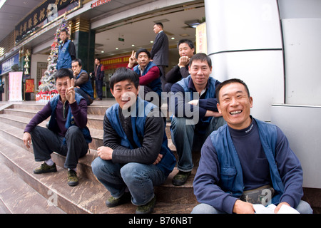 These workers smile for the camera optimistically China has been through many hard periods and has always worked - Stock Photo