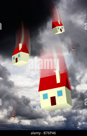 Falling houses against a stormy sky representing housing market values and repossession - digital composite - Stock Photo