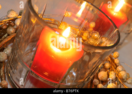 Red lighted candles in jars with garland christmas holiday decorations. - Stock Photo